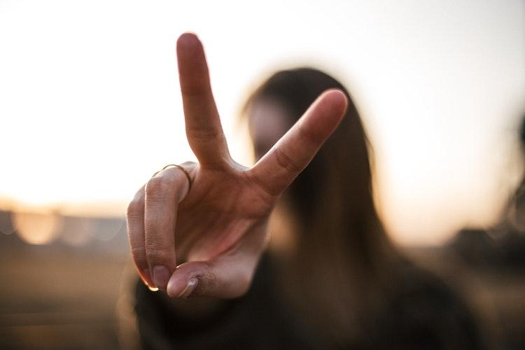 Nuori nainen näyttää rauhanmerkkiä